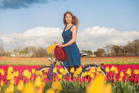 dutch girl: Beautiful woman standing with her bicycle in a yellow and red tulips field at sunset. Stock Photo