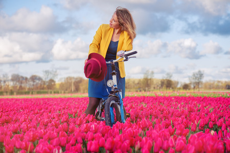 tulip: Uśmiechnięta kobieta stojąca z jej rower w żółte i czerwone tulipany pola na zachód słońca.