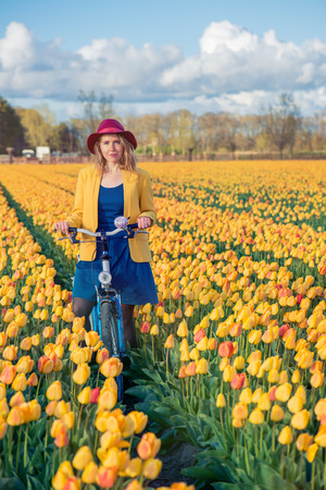 dutch girl: Smiling young woman cycling in a yellow tulips spring field on a sunny day