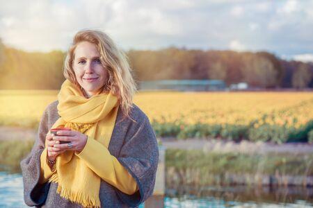 Porträt einer ruhigen Frau im Poncho und im Schal, der eine Schale mit heißem Tee in der Landschaft hält. Im Hintergrund liegen gelbe Tulpenfelder. Standard-Bild