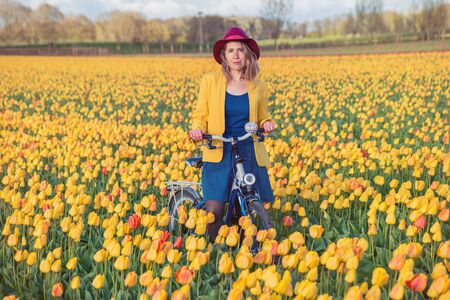 dutch girl: Smiling woman standing with her bike in a yellow and red tulips field at sunset.