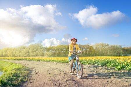 dutch girl: Cycling in the countryside - tourist in bicycle riding slong tulip fields in the Netherlands