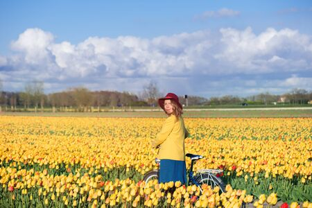 dutch girl: Smiling tourist standing with her bike in a yellow tulips field at sunset.