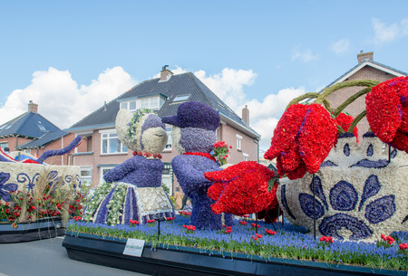 made in netherlands: HILLEGOM, THE NETHERLANDS - APRIL 23, 2016: Moving platform with a huge frame made in a form of a traditional Dutch kissing couple and vase with tulips.  Every carcass is decorated with spring flowers. Taking part in the  traditional flowers parade Bloem
