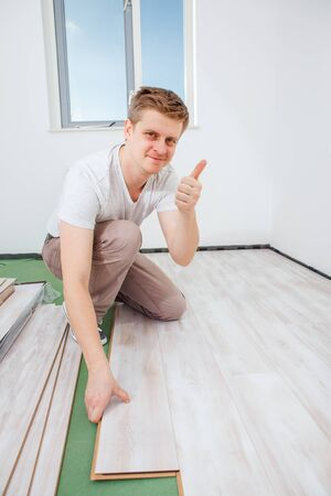 durable: Carpenter installing light laminate flooring in a room and showing a thumb up