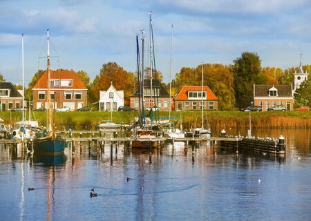 dutch typical: Typical Dutch countryside in autumn with yachts in the foreground