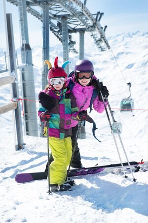 kids at the ski lift: Active mother and daughter standing with skis high in winter mountains. Cableway is in the background Stock Photo