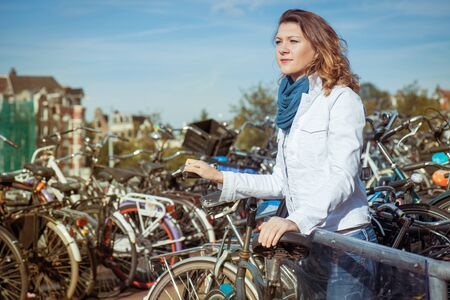 bike parking: Woman with a key unlocking her bicycle at a huge bike parking in Amsterdam