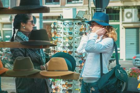 chicas de compras: Freinds en el exterior sombreros de la elección de mercado