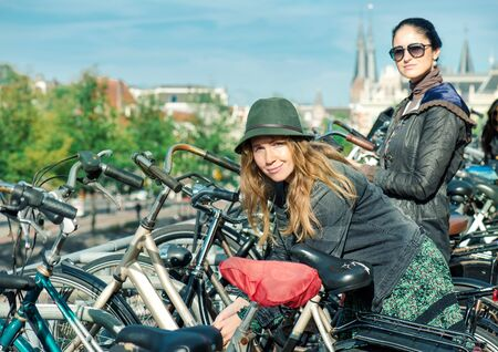 Two women locking their bikes at big cycling parking in Amsterdam, Dutch capital Stock Photo