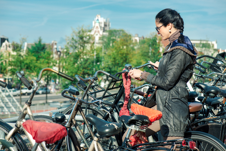 unlocking: Woman unlocking her bicycle at a huge bike parking in Amsterdam