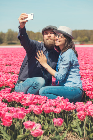 noord: Young couple making selfie in a tulip field typical for one of Dutch regions, Noord Holland