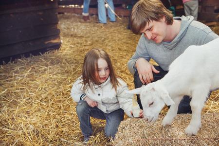 子と父の餌と、農場でヤギの子供を使いこなす 写真素材