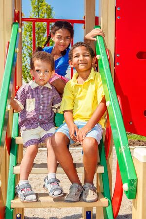 Three smiling kids enjoying summer at the outdoor playground photo