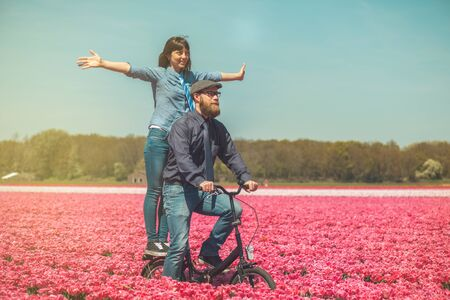dutch girl: Happy loving couple cycling through a typical Dutch tulips field in spring Stock Photo