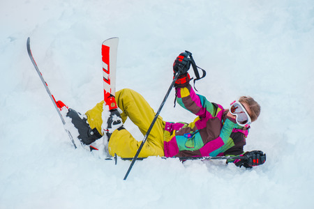 Young skier in winter sports gear lying in snow Stock Photo