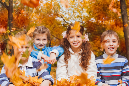 Cheerful group of kids of school age playing with yellow leaves in an autumn park photo