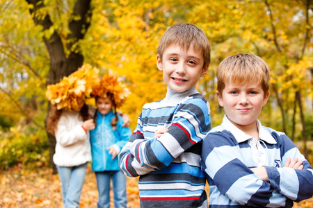 Portrait of two boys of a school age and two girls standing behind in an autumn park photo