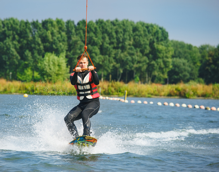 life jacket: Wakeboarder in a swimsuit and life jacket being cable towed
