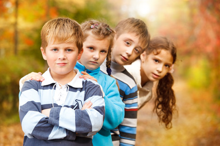 Group of children standing in a row in a beautiful park full of autumn colours Stock Photo