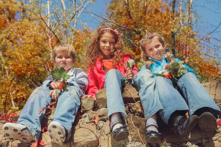 Three smiling kids sitting on a stone wall in an autumn garden photo