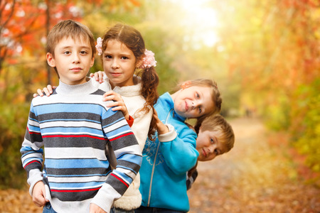 'hide out': Group of a school aged friends in an autumn park Stock Photo