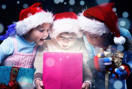 Verrast kinderen schreeuwen tegen de opening van een huidige doos magische licht binnen Stockfoto