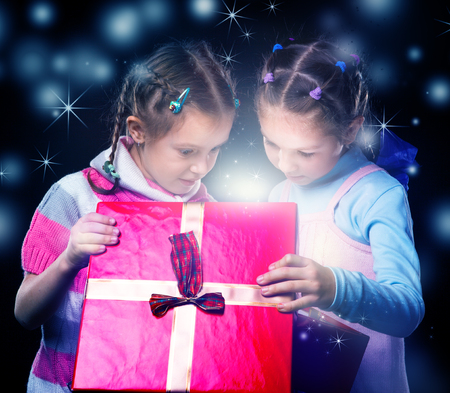 Kids surprised to open a present box magic light inside photo