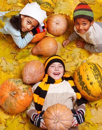 Cheerful kids of the school age lie among yellow leaves and orange pumpkings photo