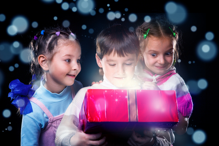 Happy kids surprised to open a present box magic light inside photo
