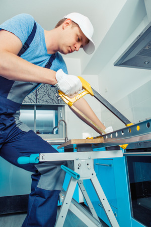 hacksaw: Handyman  in protective professional clothes cutting steel with a hacksaw Stock Photo