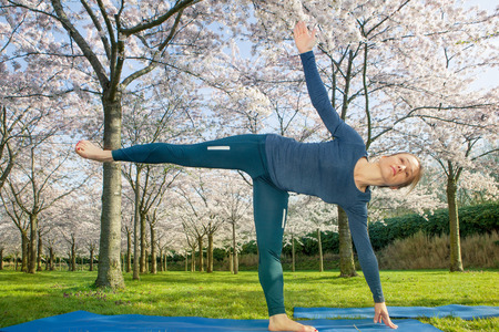 coordination: Young woman practising a half moon pose in a spring park. This pose helps to improve coordination and sense of balance Stock Photo