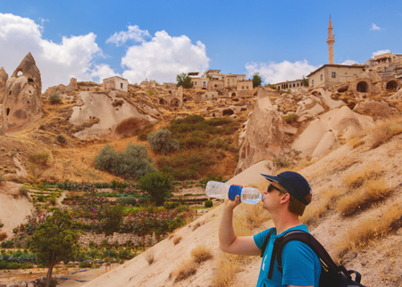touring: Tourist drinking bottled water among cave rocks in Cappadocia, a historical region in Central Anatolia, Turkey