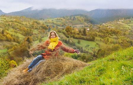 Happy tourist sitting in hay in autumn, Transylvania area, Romania