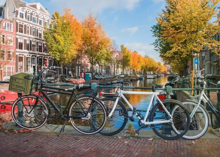 Bicycles standing near spectacular Amsterdam canals in autumn Foto de archivo