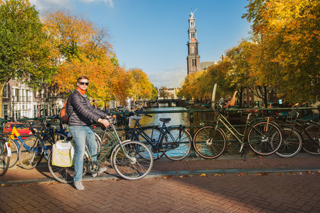Tourist cycling in the streets and along canals of Amsterdam, Netherlands, in autumn