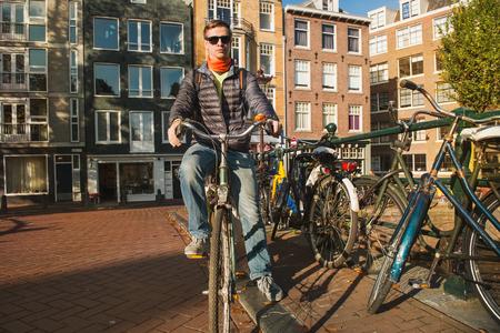 Man cycling along streets of Amsterdam Foto de archivo