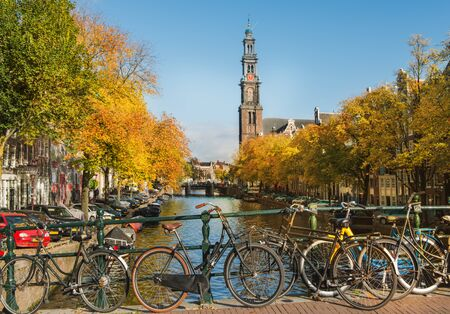 Bicycles standing near scenic Amsterdam canal in autumn. Famous Westerkerk is in the background Foto de archivo