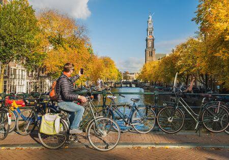 Tourist on a bike taking photo of Westerkerk in Amsterdam, Netherlands