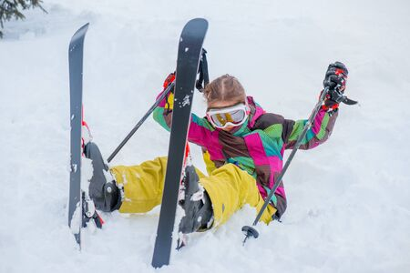 winter holiday: Happy kid sitting in snow with skis on