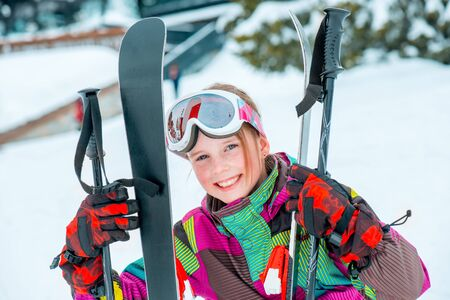 Happy kid holding skis and ski poles  in hands, sitting in snow