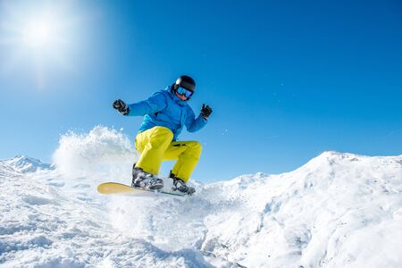 Snowboarder jumping in the mountains in winter Foto de archivo