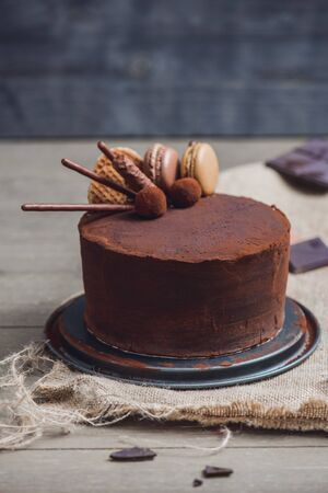 Chocolate cake covered with cocoa powder and decorated with macarons, caramel waffles, truffles and cookie sticks Foto de archivo
