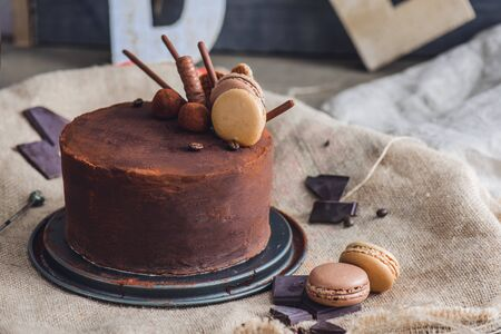 Chocolate cake covered with cocoa powder, macarons and chocolate pieces lying around on the sackcloth Foto de archivo