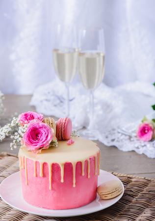 Homemade wedding cake closeup, decorated with raspberry and cream French macarons  Foto de archivo