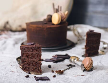 Slice of an ultimate chocolate cake, French macaron, cocoa and coffee beans  Foto de archivo