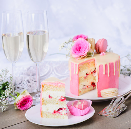 Wedding cake with pink frosting and white chocolate ganache, decorated with flowers and macaroons. Wedding gown in the background