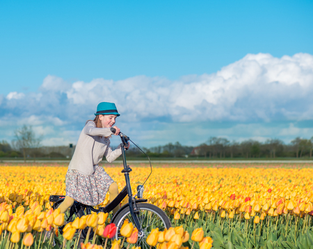 dutch girl: Happy smiling kid riding a bike in a yellow tulips field on a sunny day Stock Photo