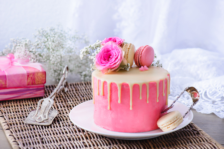 Pink cake with French macarons and flowers on top, vintage pastry tongs and present box Foto de archivo