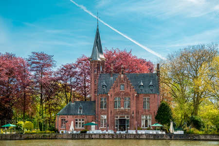Minnewater castle at the Lake of Love in Bruges, Belgium Foto de archivo